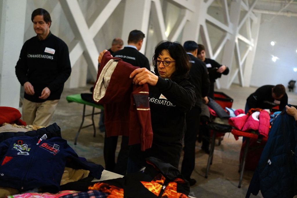 Volunteers sort coats at the annual New York Cares coat drive on December 16, 2013.