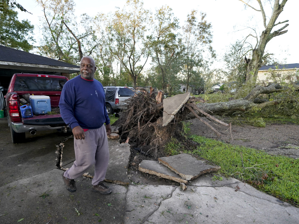 Marcus Peterson walks past a downed tree in his yard in Jennings, La. after Hurricane Delta moved through the region. Delta hit as a Category 2 hurricane with top winds of 100 mph before rapidly weakening over land.
