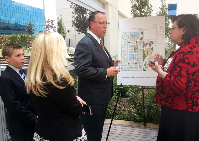Noah Kemp and his parents Kristen and Derek Kemp check out the floor plan for the new Children's Hospital of Orange County Pediatric Mental Health Center with Dr. Heather Huszti, chief psychologist at CHOC. The 18 beds at the center will be the first in the county that will be available to kids under 12.