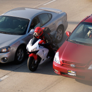 A motorcyclist slips between two cars in traffic.  This trick is called lane splitting, and California is the only U.S. state that allows it.