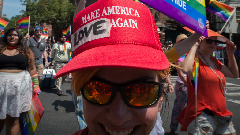 President Trump has decided to leave in place President Obama's 2014 executive order protecting employees from anti-LGBTQ workplace discrimination while working for federal contractors. Here, a marcher in New York's  Gay Pride march wears a modified version of a Trump campaign hat last summer.