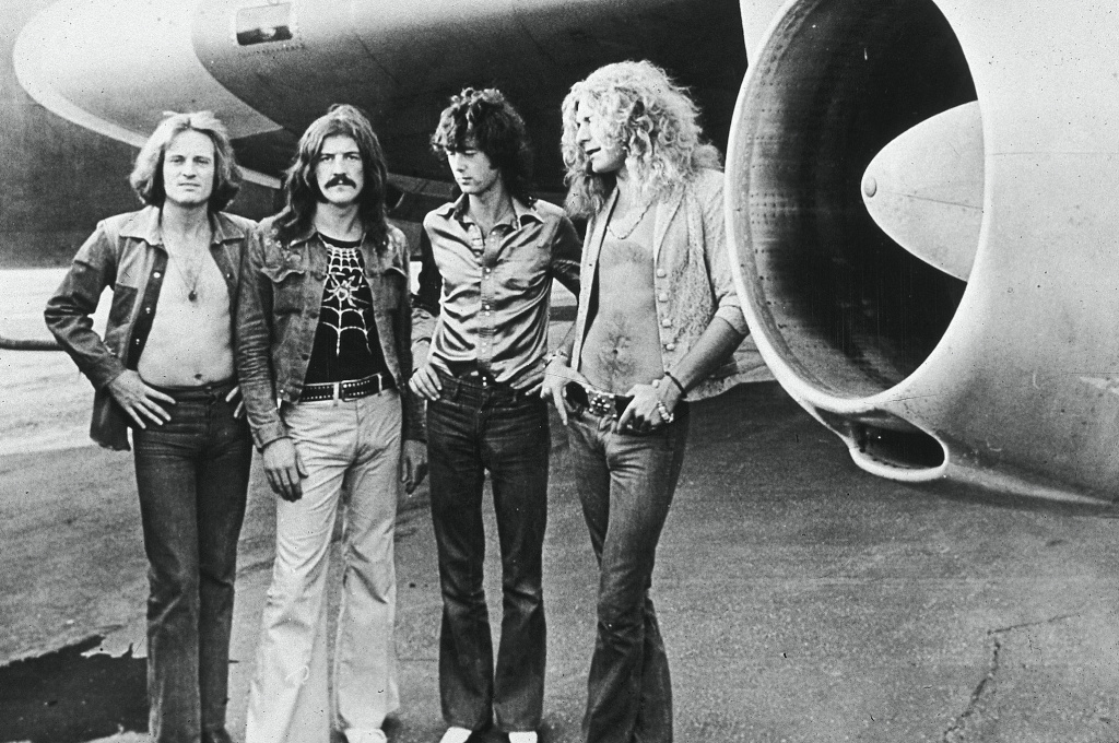 Led Zeppelin (L-R): John Paul Jones, now deceased John Bonham, Jimmy Page and Robert Plant, pose in front of an their private airplane in 1973.