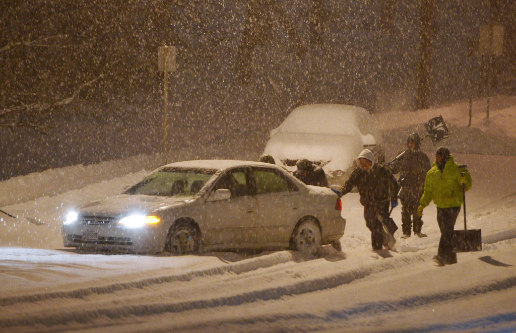 Workers help push a car which is stuck in the snow in Chevy Chase, Maryland, in the early hours of February 13, 2014. A deadly ice storm stranded scores of people on slick roads and knocked out power to hundreds of thousands of U.S. homes as winter-weary Americans dug in against Mother Nature's latest blow. The storm also caused nearly four dozen flights to be canceled at Los Angeles International Airport early Thursday.