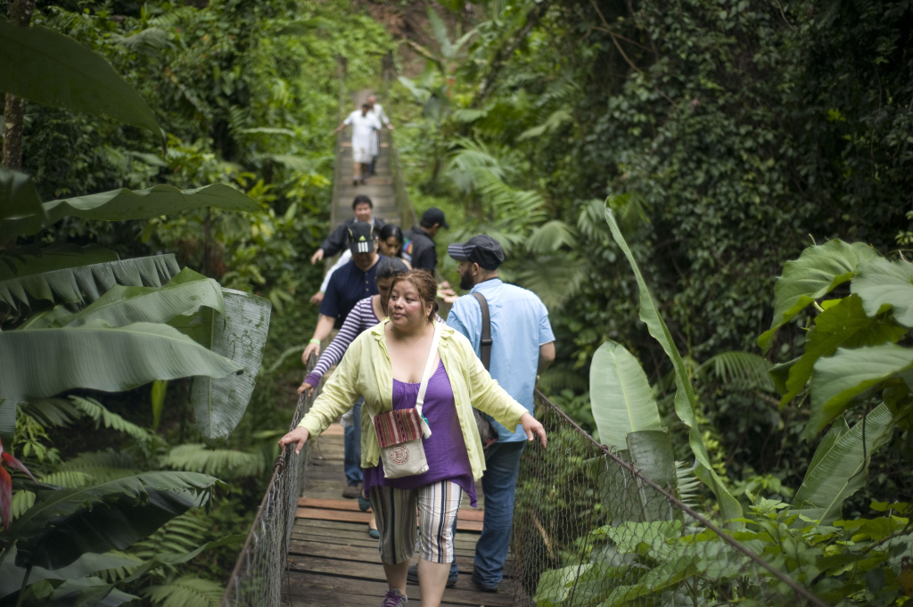 People walk on a hanging bridge in the Patrocinio Natural Reserve in the Quetzaltenango department, 196 km southwest of Guatemala City on June 22, 2012.