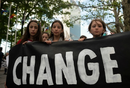 "School children hold a placard reading ""CHANGE"" during the Youth Climate Strike"