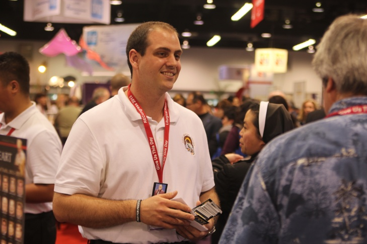 Thomas Roide, a 25-year-old seminarian from La Crescenta, Calif., hands out pray cards at the Los Angeles Religious Education Congress at the Anaheim Convention Center on Saturday, Feb. 23.