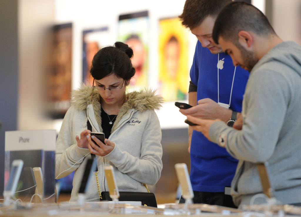 A woman looks at the new iPhone 5S at the Apple Store at the Americana at Brand shopping complex in Glendale, California, September 20, 2013 to buy the new Apple iPhones. Apple launched two new models of the iPhone today - the iPhone 5S, which is an updated version of the iPhone 5, and a less expensive version, the iPhone 5C.