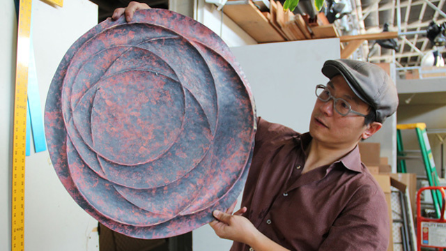 Artist Nick Dong displays a copper wall hanging he's making at American Steel.