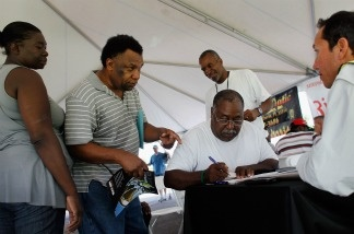 Job seekers speak with a construction company recruiter as they and others look for construction work.