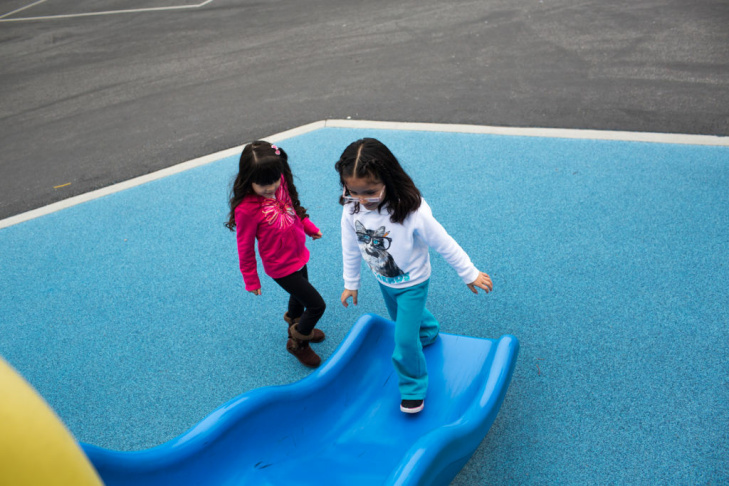 Vanessa Delgado, left, and Ashley Vargas play on a slide at the Martha Escutia Primary Center where they attend transitional kindergarten.