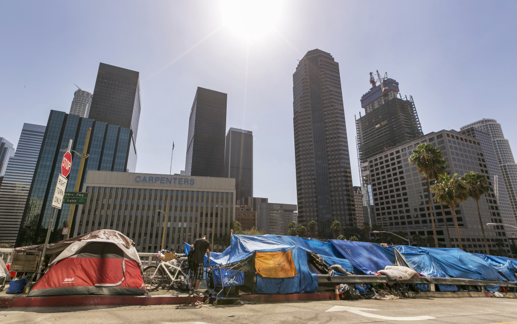 Tents used by the homeless line a downtown Los Angeles street with the skyline behind Tuesday, Sept. 22, 2015.