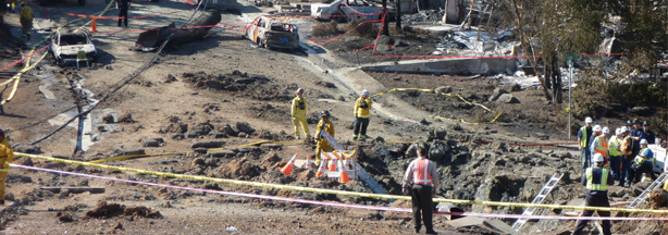 Accident scene with the crater in the foreground and the ruptured pipe section in the background