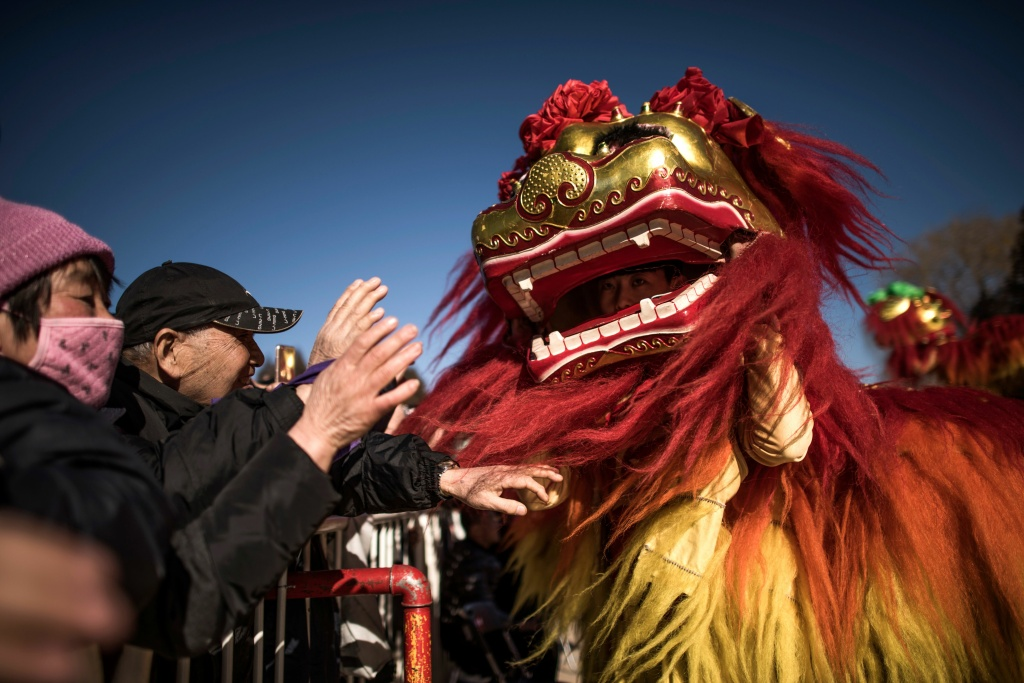 Spectators touch an actor performing the lion dance in Ditan park during Lunar New Year celebrations in Beijing on February 1, 2017.