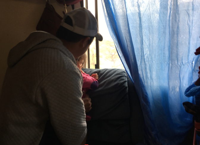 Marvin, an unauthorized immigrant from Honduras, looks out the window of his family's tiny studio apartment with his young daughter. The family has been in the United States for less than two years. They say they fled gang violence and extortion and are seeking asylum. But he and his wife fear they could be deported.