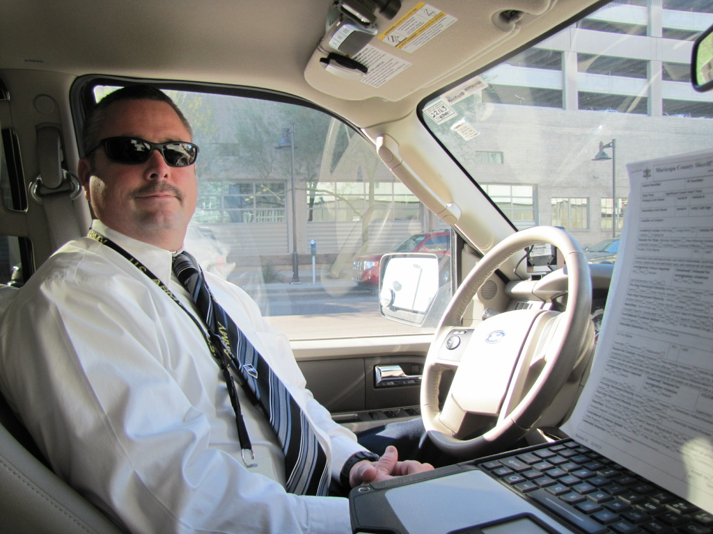 Sgt. Christopher Dowell in his patrol vehicle. The form on the right has all of the information deputies must record after each contact with the public.