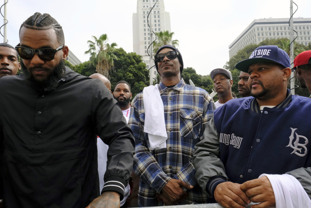 Rappers The Game, left, and Snoop Dogg, center, appear at a peaceful unification march outside of the graduation ceremony for the latest class of Los Angeles Police recruits in Los Angeles, Friday, July 8, 2016. Snoop shook hands with police officials and told reporters he hoped his presence would help reintroduce the black community to the Police Department and open a dialogue. The gathering comes a day after the shooting deaths of multiple police officers in Dallas on Thursday night.
