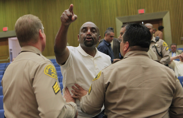 Rev. Jesse Lee Peterson, president and founder of The Brotherhood Organization of A New Destiny, middle, protests against Supervisor Mark Ridley-Thomas' vote, as he is asked to leave the hall by Los Angeles Sheriffs, after Los Angeles County Board of Supervisors voted 3-2 to join the city in its economic boycott of Arizona over its SB 1070 law targeting illegal immigrants, on Tuesday, Jun 1, 2010, in Los Angeles.