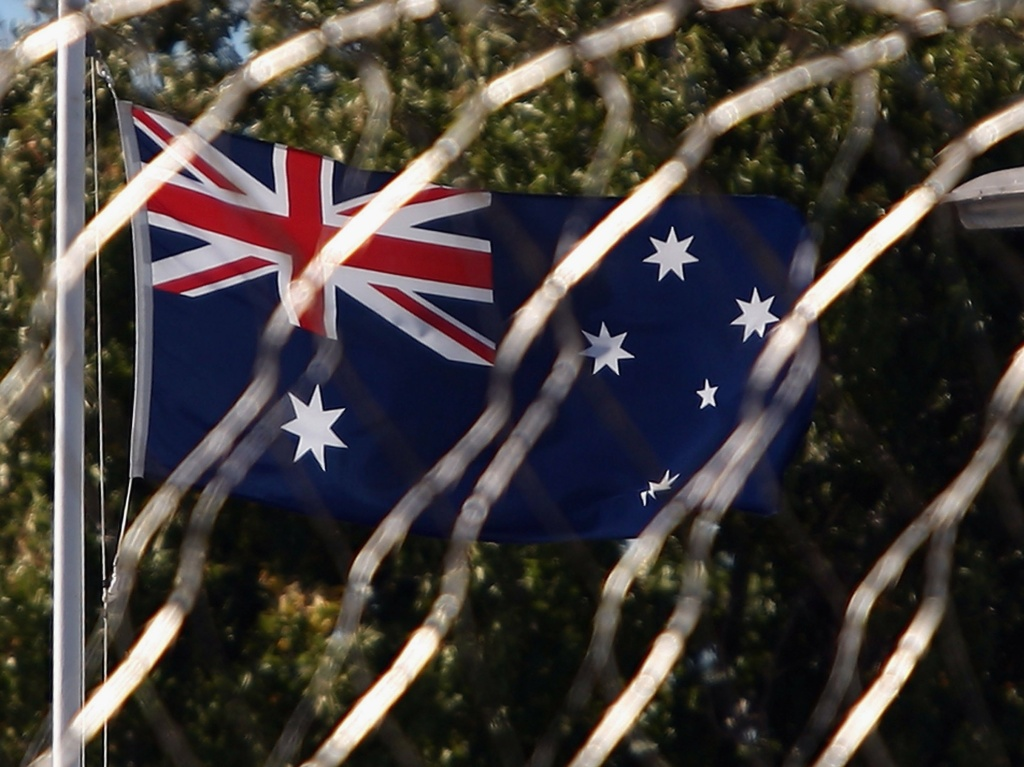An Australian flag flies outside Bandyup Women's Prison where a woman was forced to give birth alone in a locked prison cell despite pleading for help for more than an hour, according to a newly released report.
