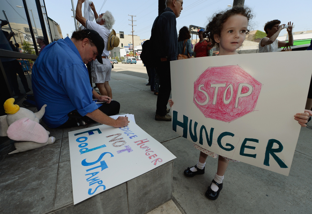 Gracie Shannon-Sanborn, 5, holds a sign as she joins her father Allen Sanborn (L) and members of Progressive Democrats of America and other activists as they hold a rally in front of Rep. Henry Waxman's office on June 17, 2013 in Los Angeles, California. The protestors were  asking the congressman to vote against a House farm bill that would reduce federal spending on the Supplemental Nutritional Assistance Program by $20.5 billion and affect food stamps and other services for the poor.