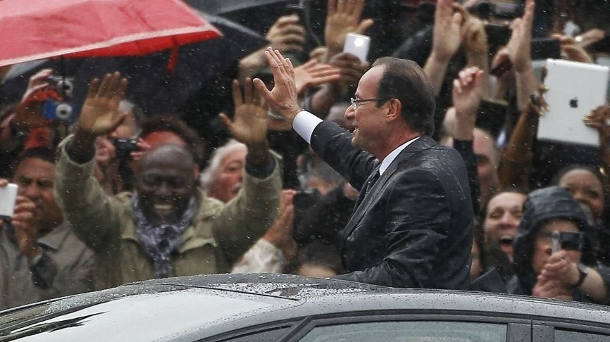 Francois Hollande stands up in his car Tuesday as he rides up the Champs-Elysees after taking the oath of office as the new president of France.