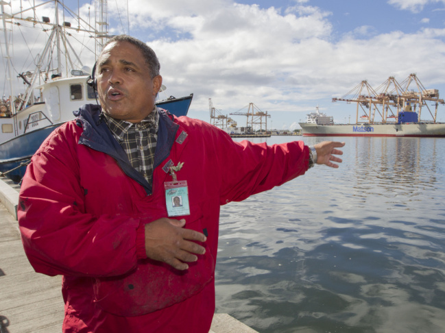 John Hernandez of Kailua, Hawaii and owner of John's Fresh Fish, is shown on Thursday. In the background at right is a container ship owned by Matson. A pipe  maintained by the company cracked and caused the molasses spill.