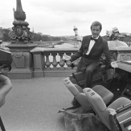 British actor Roger Moore on set of the James Bond movie 'A View to a Kill' with half a car during filming in Paris, France in August 1984.