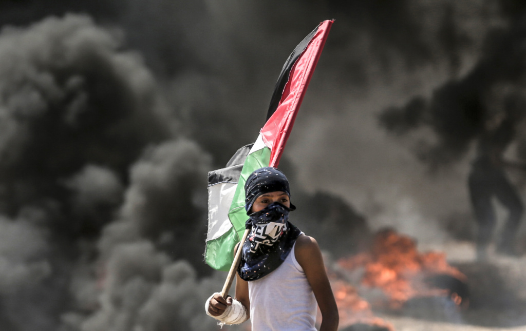 A Palestinian boy holding his national flag looks at clashes with Israeli security forces near the border between the Gaza Strip and Israel east of Gaza City on May 14, 2018, as Palestinians protest over the inauguration of the US embassy following its controversial move to Jerusalem.