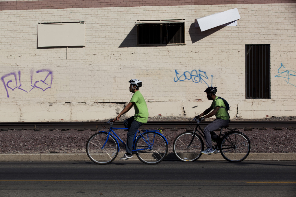 File: Victor Aquino and Malcolm Harris bike along Slauson Avenue in South Los Angeles, navigating traffic and unsafe conditions.