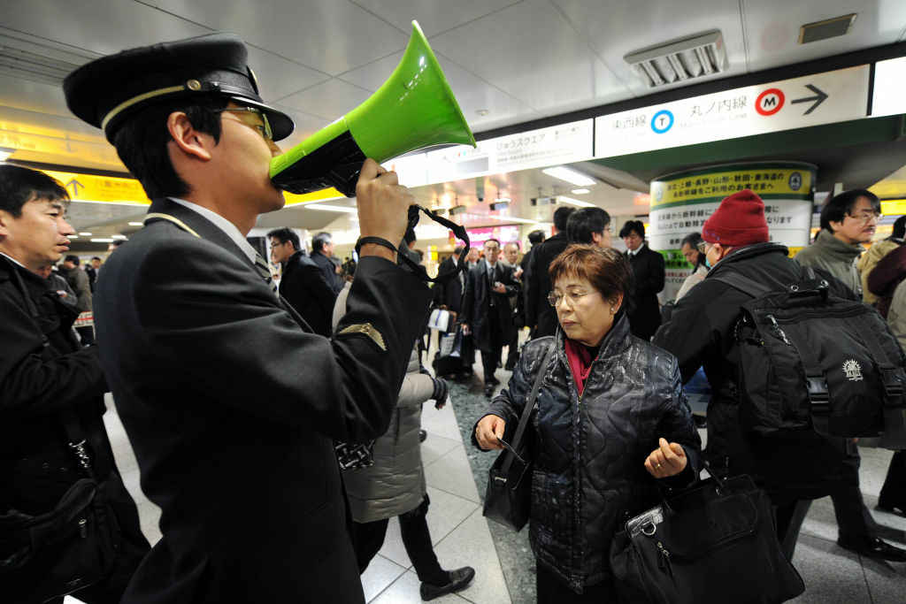 A station attendant uses a loudspeaker to explain the train service situations for the Tohoku Shinkansen (bullet train) which connects Tokyo and northern Japan at Tokyo Station on December 7, 2012 following a 7.3 earthquake and tsunami alert. A one metre-high tsunami hit northeast Japan after a powerful undersea quake struck off the coast which was devastated in last year's quake-tsunami disaster.