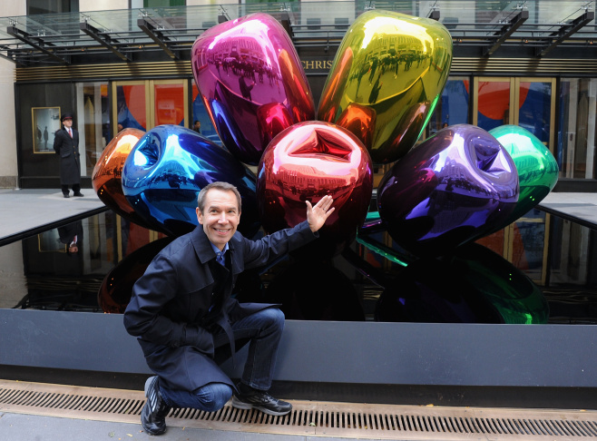 Artist Jeff Koons poses with his sculpture