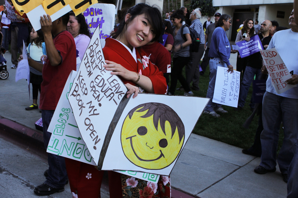 A protester holds a sign at a rally outside of LAUSD headquarters at an adult education rally in downtown Los Angeles.
