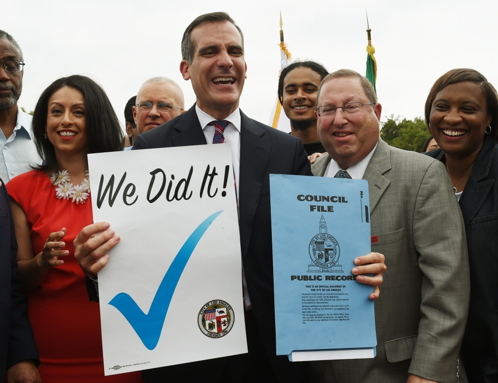 Los Angeles Mayor Eric Garcetti (C) celebrates with City Councilors and labor representatives after he signed into law an ordinance raising the minimum wage to USD 15 an hour by 2020, in Los Angeles, California on June 13, 2015.