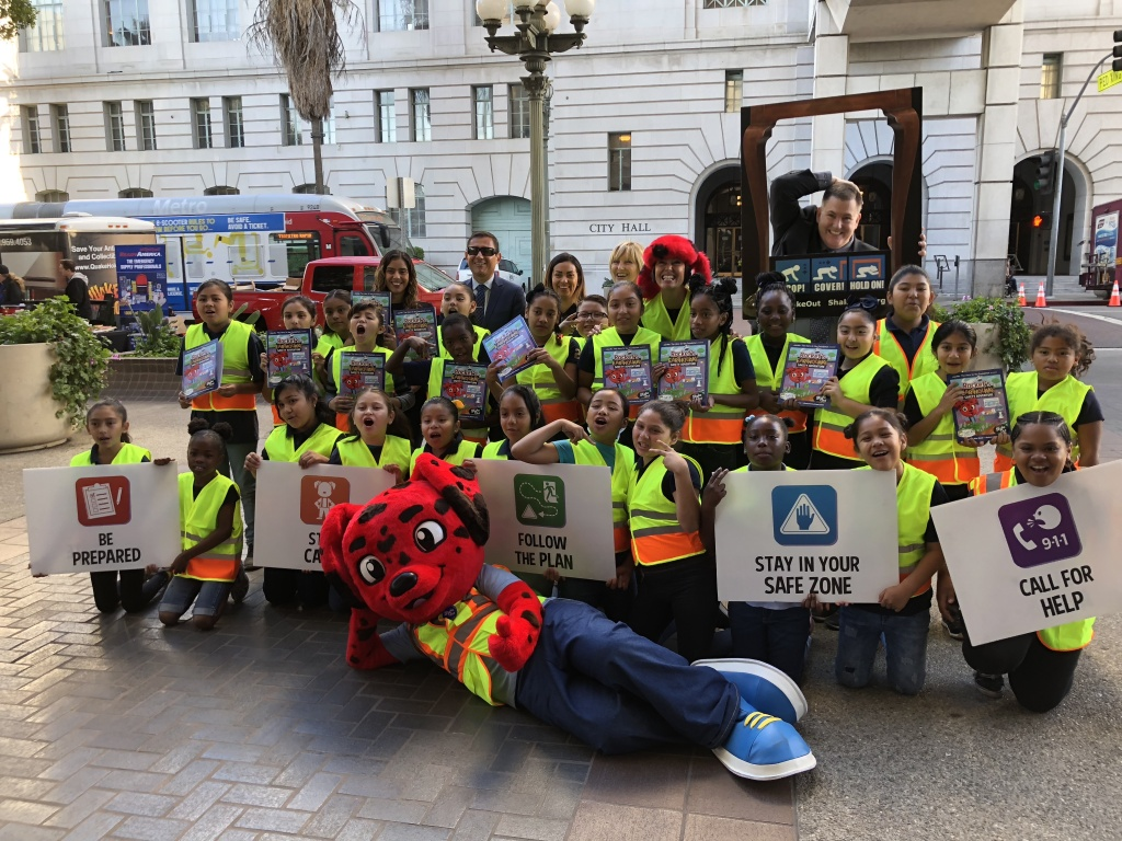 Officials and Holmes Avenue Elementary students pose with Rocket in front of City Hall before the Great ShakeOut earthquake drill.