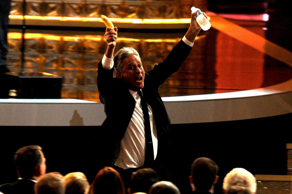 TV host Jon Stewart (holding a banana and water) runs to his seat during the 64th Annual Primetime Emmy Awards at Nokia Theatre L.A. Live on September 23, 2012 in Los Angeles, California.