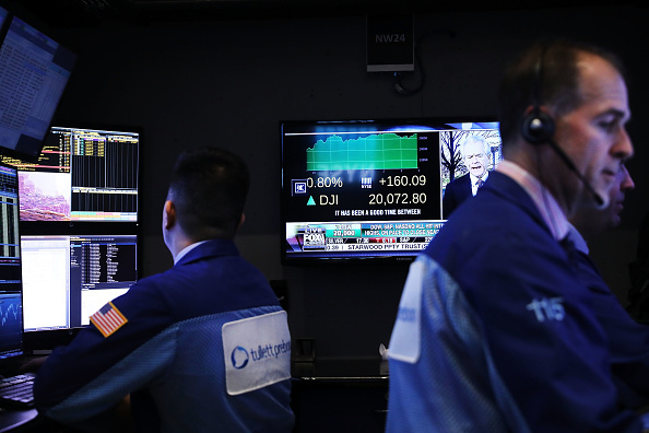 Traders work on the floor of the New York Stock Exchange (NYSE) as the Dow Jones industrial average closed above the 20,000 mark for the first time on January 25, 2017 in New York City.
