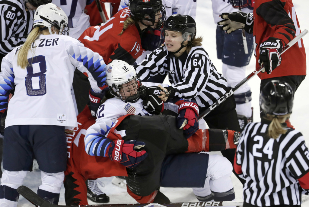 Official Jenni Heikkinen (No. 64) of Finland tries to separate women's hockey players Kelly Pannek (No. 12) of the United States and Laura Stacey (No. 7) of Canada as they scuffle at the 2018 Pyeongchang Winter Olympics.