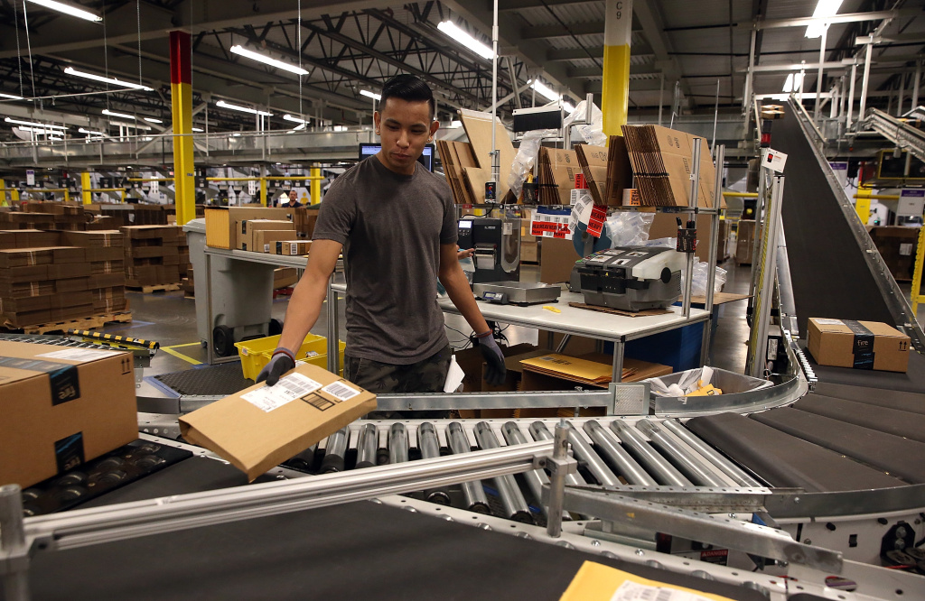 File: An Amazon.com worker sorts packages onto a conveyor belt at an Amazon fulfillment center on January 20, 2015 in Tracy, California.