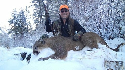 Richards poses with the now-dead mountain lion, which he later ate.