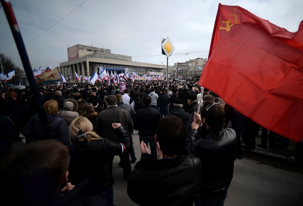 A man holds a Soviet Union flag during a pro-Russia rally in Simferopol, Crimea's Lenin Square Sunday. In Kiev, Ukrainian Prime Minister Arseniy Yatsenyuk vows not to give