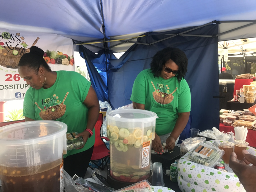 Javonne Sanders, left, serves salads and juice using fresh produce with her local business, Toss It Up.