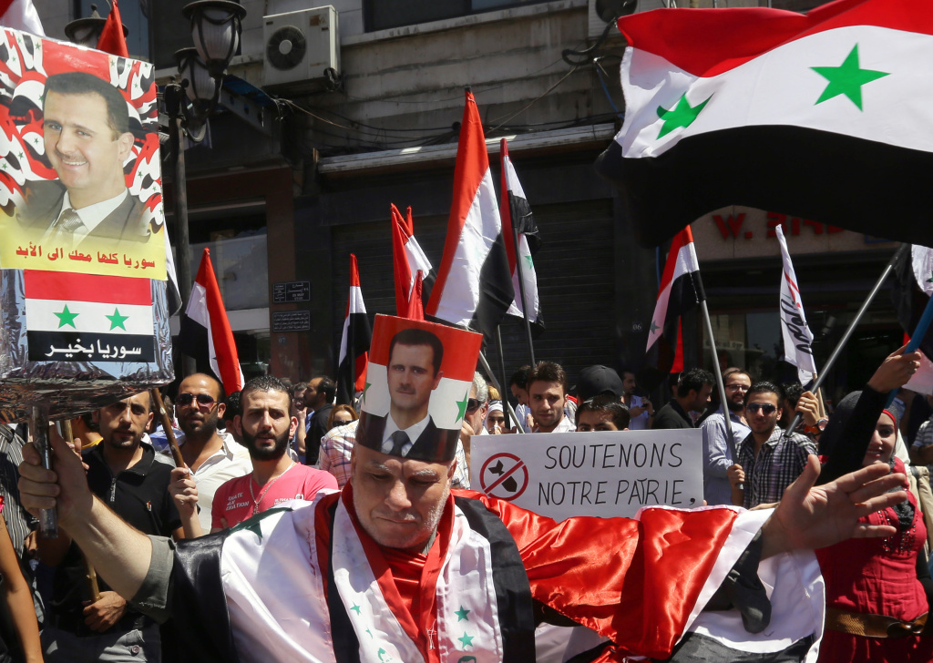 A protester, wearing a poster wrapped on his head with the portrait of the Syrian president and draped in a Syrian national flag, takes part in a rally to show support to Syrian President Bashar al-Assad on September 9, 2013 in Damascus.