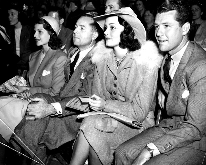 Rita Hayworth, Edward Judson, Doune McKay, and Gordon Oliver watching the Roller Derby at the Pan-Pacific Auditorium. Photograph dated July 23, 1938.