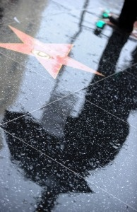 The silhouette of a man walking through the rain with an umbrella on Hollywood boulevard is seen in Hollywood, California.