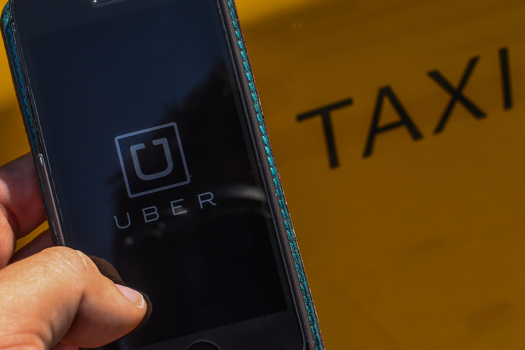 In this photo illustration, the new smart phone app 'Uber' logo is displayed on a mobile phone next to a taxi on July 1, 2014.