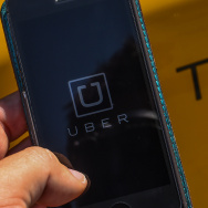 In this photo illustration, the new smart phone app 'Uber' logo is displayed on a mobile phone next to a taxi on July 1, 2014 in Barcelona, Spain.