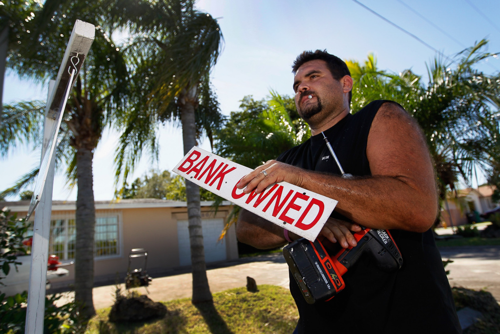 MIAMI, FL - NOVEMBER 10:  Renzo Salazar, from Real Signs of Ace Post Holding Inc., places a bank owned sign on top of a for sale sign in front of a foreclosed home on November 10, 2011 in Miami, Florida.