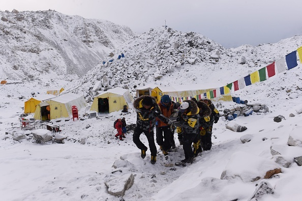 An injured person is carried by rescue members to be airlifted by rescue helicopter at Everest Base Camp a day after an avalanche triggered by an earthquake devastated the camp.