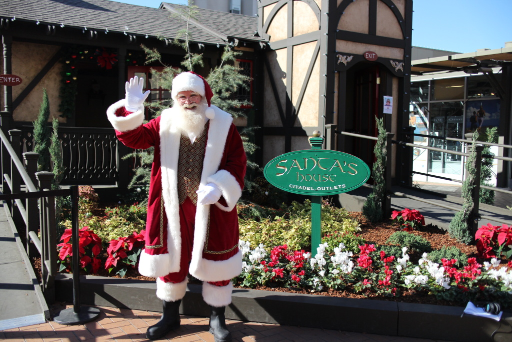 Santa stands outside of his house at the Citadel Outlets in Commerce for a Santa Cares event.