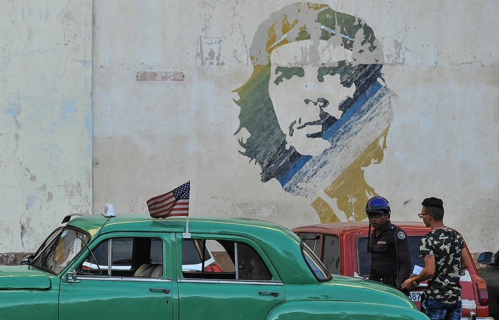 Picture of an old car with a the US flag and a graffiti of revolutionary leader Ernesto 'Che' Guevara taken in Havana, on June 16, 2017.