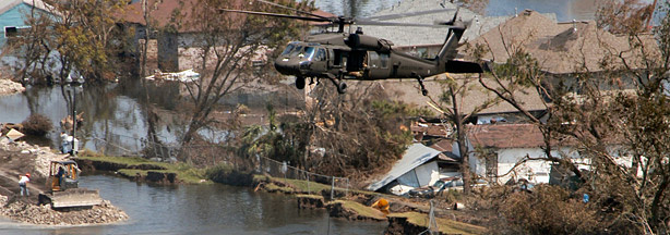 A helicopter lowers sandbags to fill the gap left behind the 17th Street levee failure.